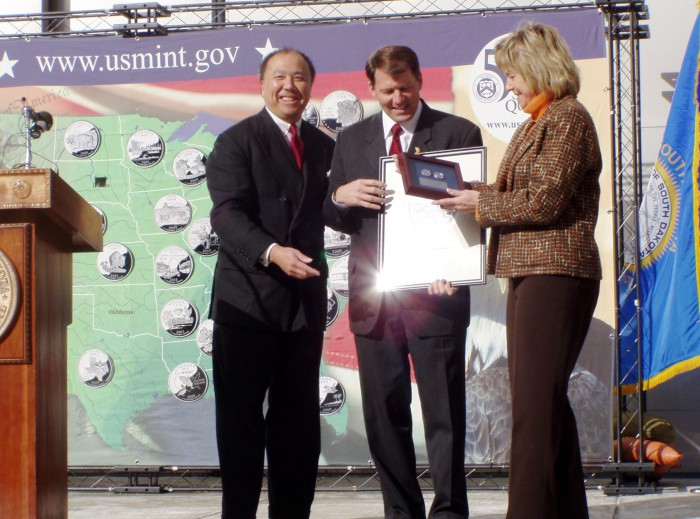 Presenting to South Dakota Governor M. Michael Rounds and First Lady Jean Rounds two South Dakota state quarters from the first day of minting and a copy of the original artwork signed by John Mercanti, who created the final design.
